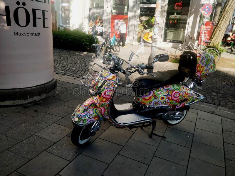 Красочно конструированное белое положение скутера дам на обочине стоковое фото