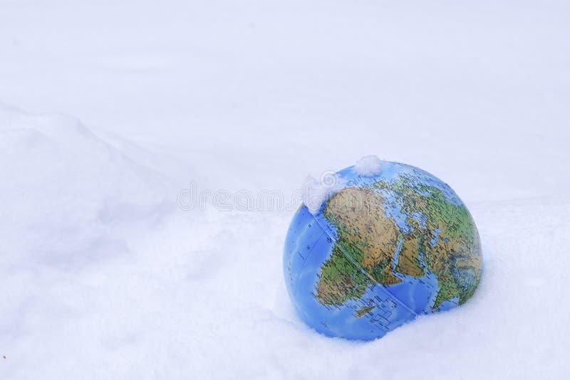Красочную землю глобуса предусматриванную в снеге, можно использовать как концепция для глобального потепления стоковая фотография rf