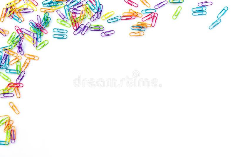 Красочные бумажные зажимы изолированные на белизне с космосом экземпляра задняя школа принципиальной схемы к стоковые изображения