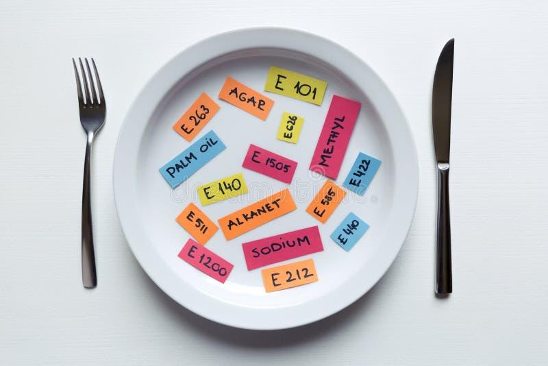 Красочные бумажные примечания называя пищевые добавки на плите с вилкой и ножом, пищевой добавкой и нездоровой концепцией еды стоковые изображения rf
