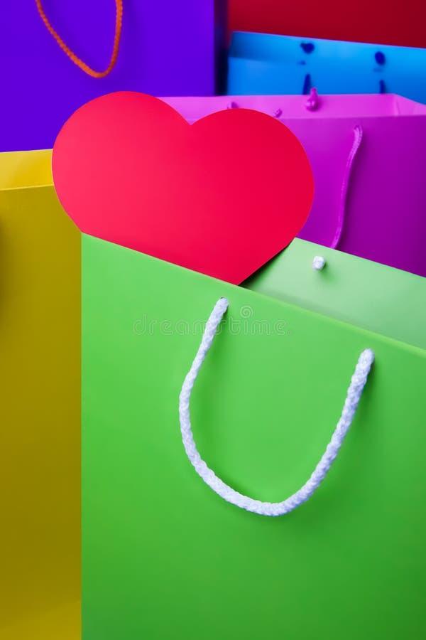 Красочные бумажные хозяйственные сумки с красным сердцем стоковое фото