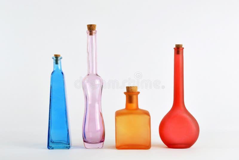 Красочные бутылки зелья на белизне стоковые фото