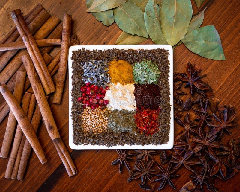 Красочные высушенные травы и семена специй центризовали на деревянной предпосылке стоковое фото
