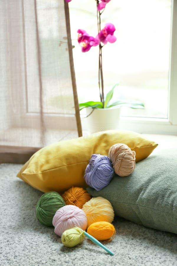 Красочные вязать пряжи и вязание крючком на ковре внутри помещения стоковое изображение