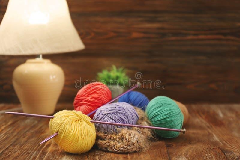Красочные вязать пряжи и иглы на деревянном столе внутри помещения стоковое фото