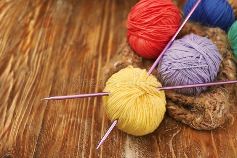 Красочные вязать пряжи и иглы на деревянном столе стоковое фото rf