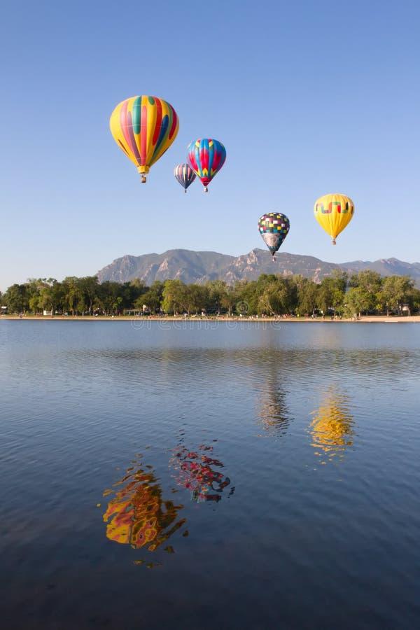 Красочные горячие воздушные шары летая над озером стоковое изображение rf