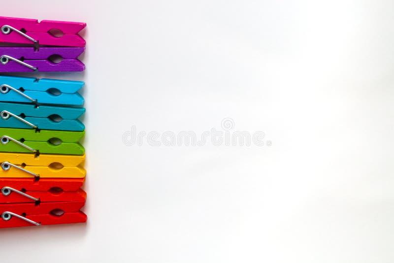 Красочные деревянные зажимки для белья на белой предпосылке с экземпляром размечают/концепцией разнообразия стоковые изображения