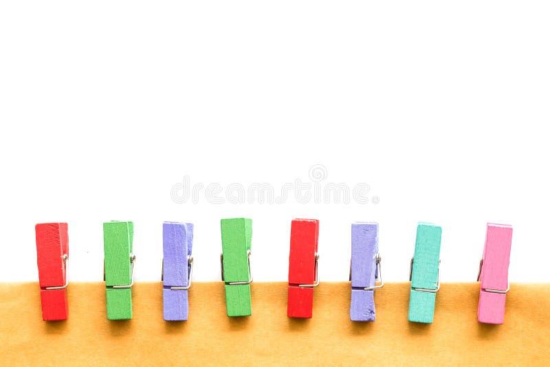 Красочные деревянные штыри и бумага изолированные на белой предпосылке стоковое изображение