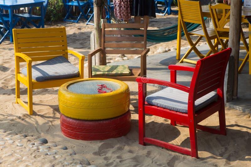 Красочные деревянные стулья и таблица на пляже стоковое фото rf