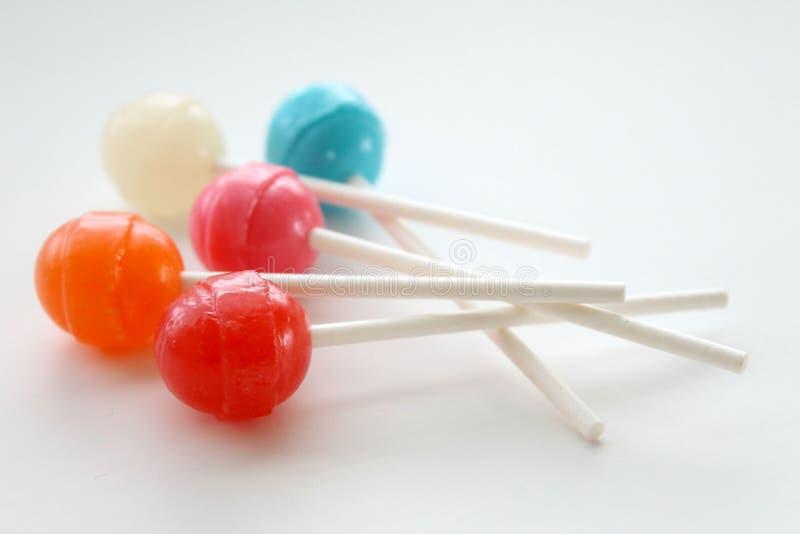 Красочные леденцы на палочке и высасыватели на белой изолированной предпосылке стоковое фото rf