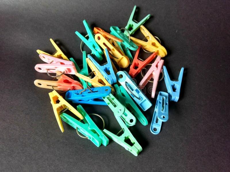 Красочные зажимки для белья с черной предпосылкой стоковое изображение rf