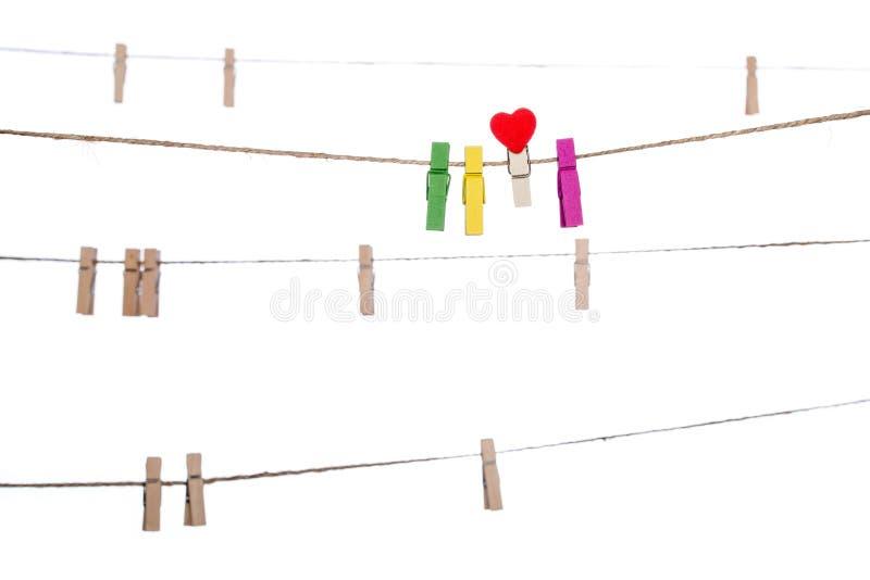 Красочные зажимки для белья с формой сердца закрепляют на веревке для белья стоковые изображения rf