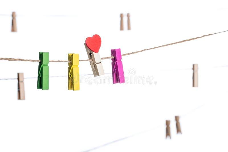 Красочные зажимки для белья с формой сердца закрепляют на веревке для белья стоковая фотография