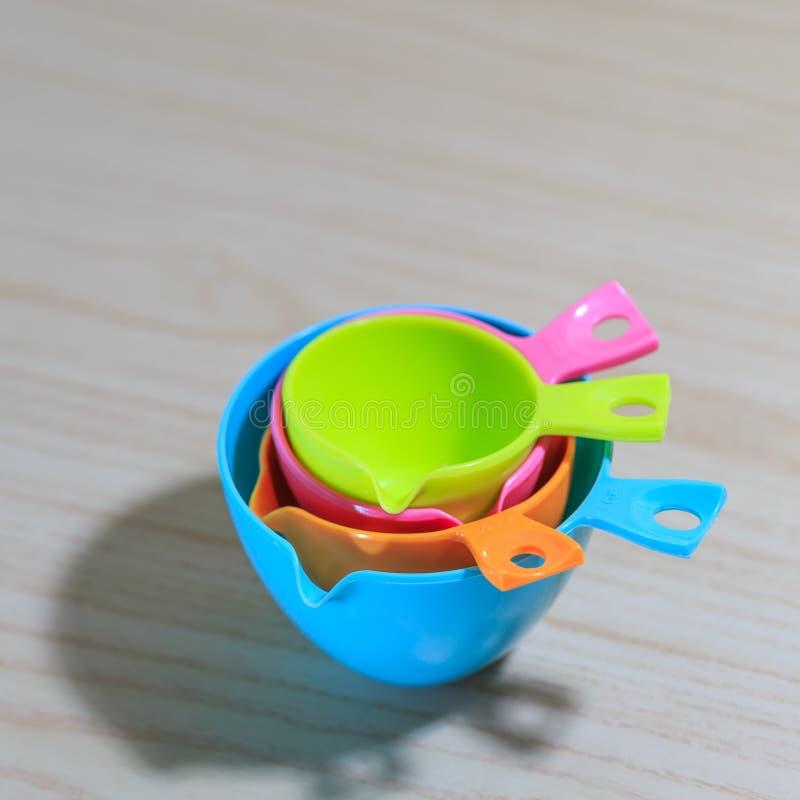 Красочные измеряя чашки изолированные на белой предпосылке деревянного стола стоковое изображение rf