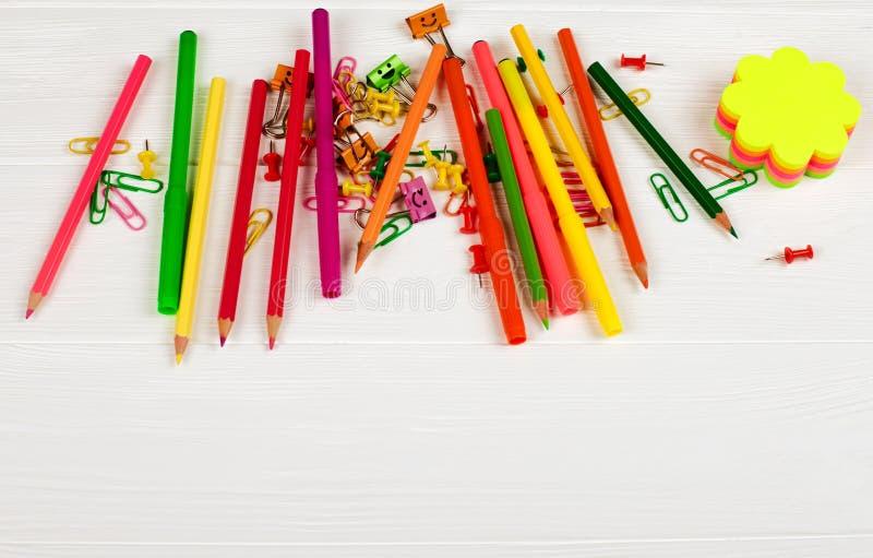 Красочные карандаши и ручки войлок-подсказки, notepapers цвета, бумажные зажимы, ногти канцелярских принадлежностей на белой дере стоковые фото