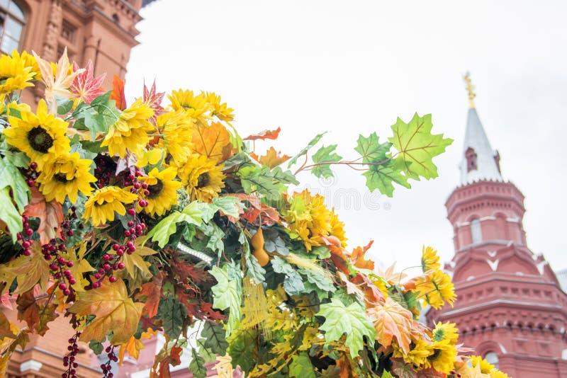 Красочные кленовые листы, солнцецветы и ягоды боярышника Красиво конструированное оформление осени на красной площади в Москве стоковая фотография
