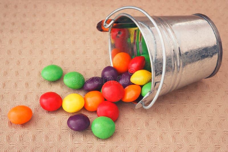 Красочные конфеты разлитые от декоративного ведра стоковая фотография rf