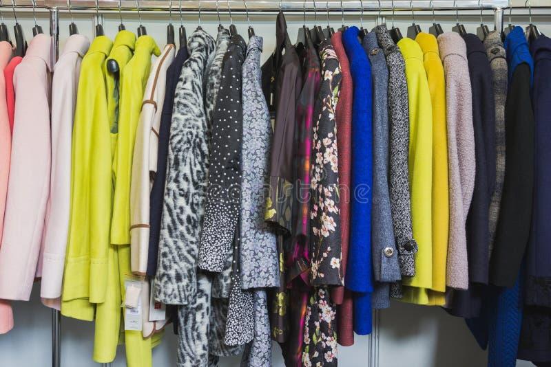 Красочные одежды в магазине одежды - платья и куртки стоковые изображения rf