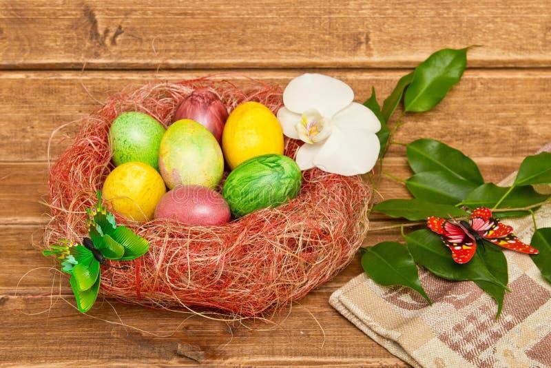 Красочные пасхальные яйца в гнезде на деревянной предпосылке Eggs handmade новый стиль расцветки стоковые фотографии rf