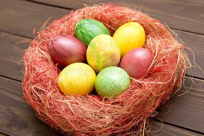 Красочные пасхальные яйца в гнезде на деревянной предпосылке Eggs handmade новый стиль расцветки стоковая фотография rf