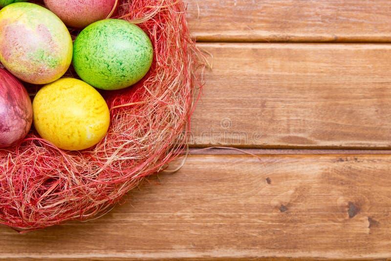 Красочные пасхальные яйца в гнезде на деревянной предпосылке Eggs handmade новый стиль расцветки стоковая фотография