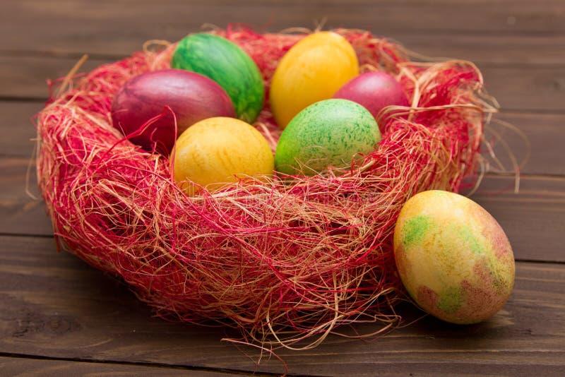 Красочные пасхальные яйца в гнезде на деревянной предпосылке Eggs handmade новый стиль расцветки Картина, концепция пасхи стоковое изображение rf