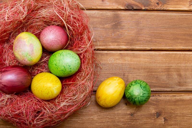 Красочные пасхальные яйца в гнезде на деревянной предпосылке Eggs handmade новый стиль расцветки Картина, концепция пасхи стоковые изображения rf
