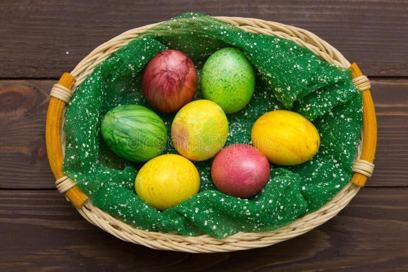 Красочные пасхальные яйца в корзине на деревянной предпосылке Eggs handmade новый стиль расцветки Картина, концепция пасхи стоковая фотография rf