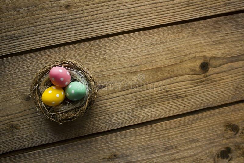 Красочные пасхальные яйца в гнезде на деревянном столе стоковая фотография