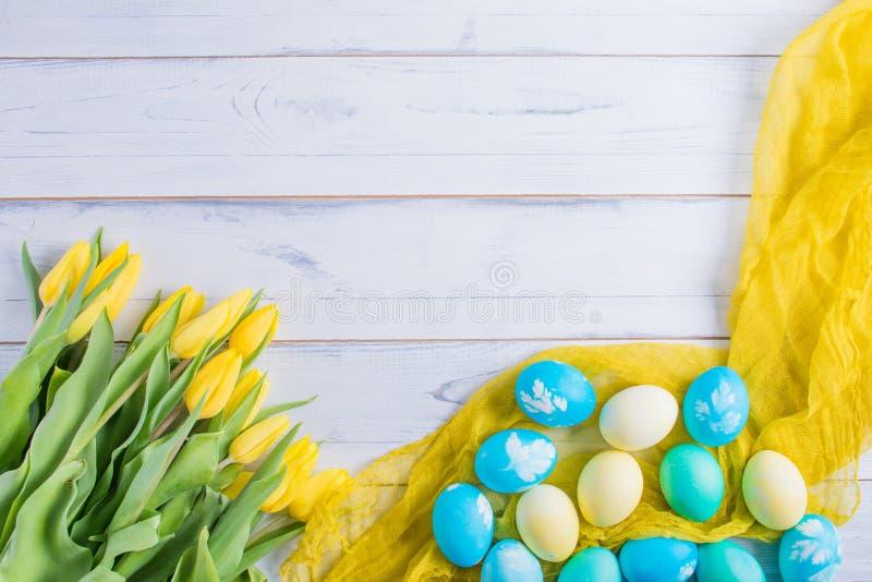 Красочные пасхальные яйца и тюльпаны на белое деревенском wdooen таблица стоковая фотография rf