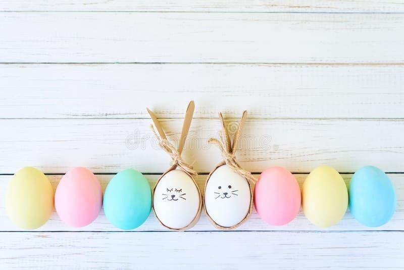 Красочные пасхальные яйца с покрашенными сторонами и ушами зайчика в строке на белой предпосылке стоковое изображение rf