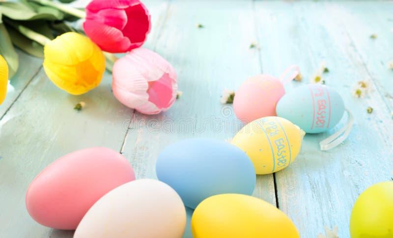 Красочные пасхальные яйца с тюльпаном цветут на деревенской деревянной предпосылке планок стоковая фотография rf