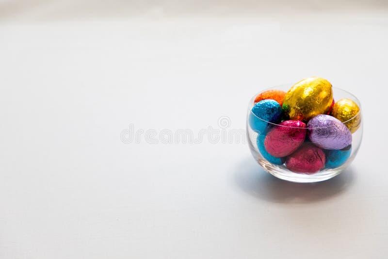 Красочные пасхальные яйца шоколада в прозрачном шаре изолированном с предпосылкой whit стоковые изображения