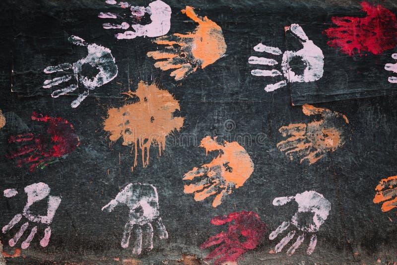 Красочные печати ладони на черной стене стоковое фото