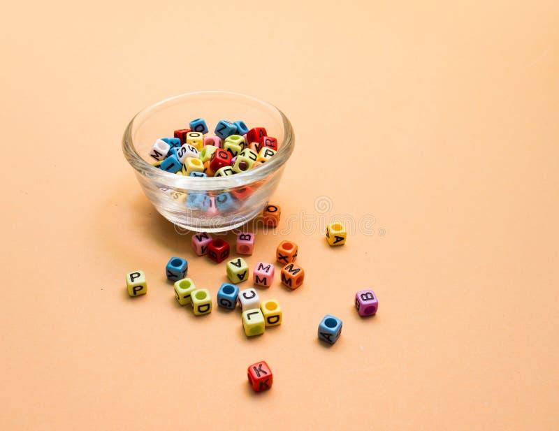 Красочные письма куба в стеклянной чашке на оранжевой предпосылке стоковая фотография