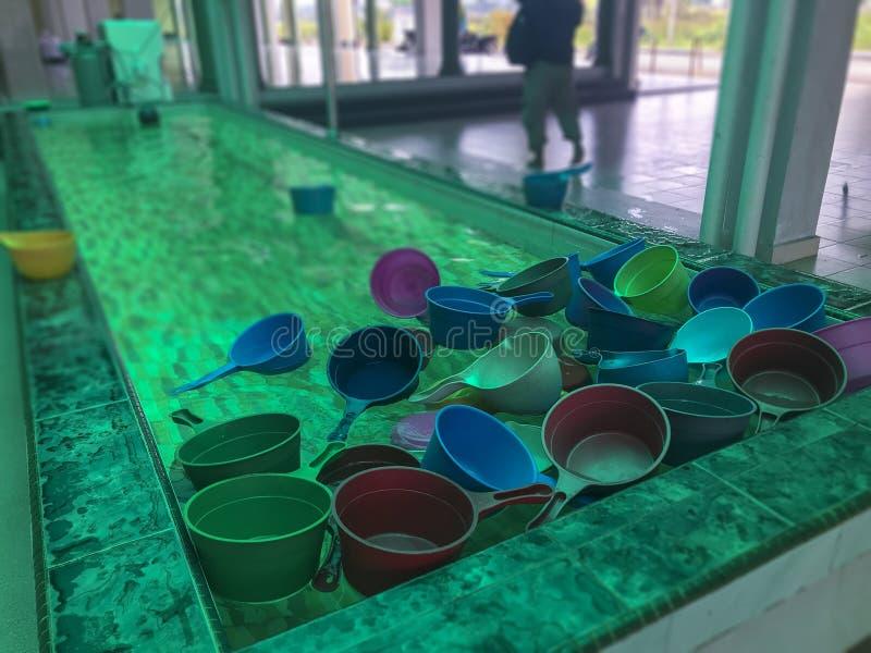 Красочные пластиковые ковши воды обычно используемые мусульманами для того чтобы зачерпнуть воду для очищения омовения перед выпо стоковое изображение rf