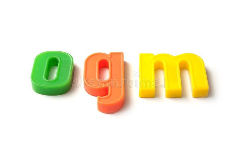 красочные пластиковые письма на белой предпосылке - ogm стоковая фотография