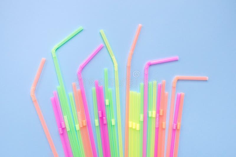 Красочные пластиковые соломы на голубой предпосылке Трубки коктейля стоковое фото rf