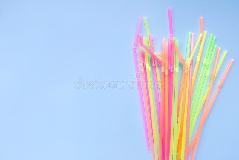 Красочные пластиковые соломы на голубой предпосылке Трубки коктейля стоковое фото