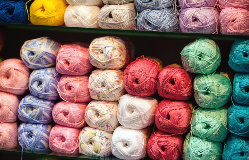 Красочные потоки Выбор красочных шерстей пряжи на shopfront Вязать предпосылка, много шарики Вязать пряжа для стоковые изображения