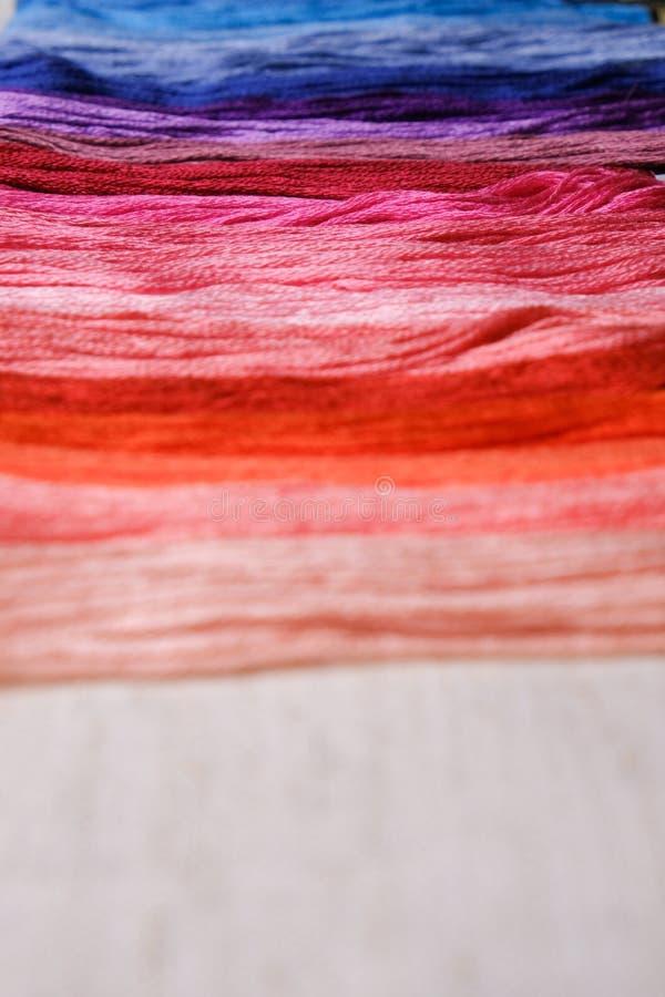 Красочные пряжи для вышивать Пестротканый поток выровнянный в ряд на предпосылке холста стоковое изображение
