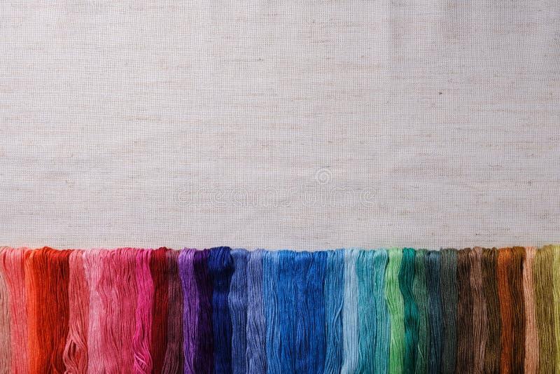 Красочные пряжи для вышивать Пестротканый поток выровнянный в ряд на предпосылке холста r стоковое фото