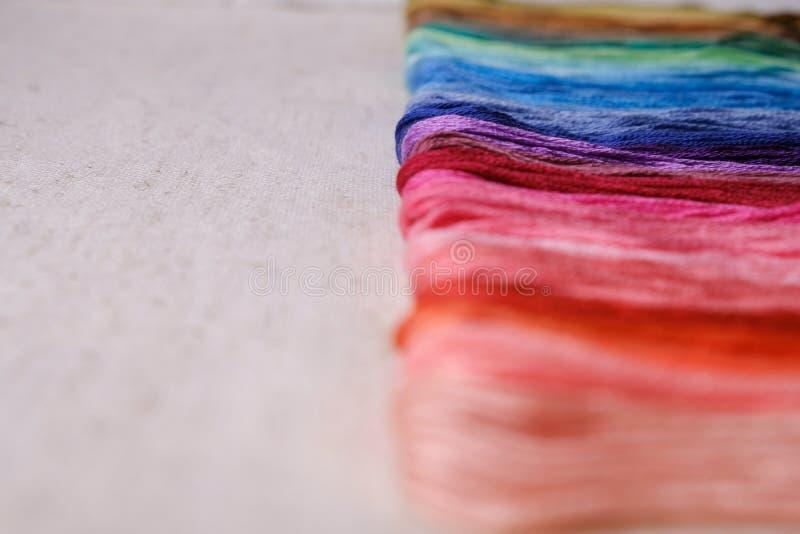 Красочные пряжи для вышивать Пестротканый поток выровнянный в ряд на предпосылке холста стоковая фотография rf
