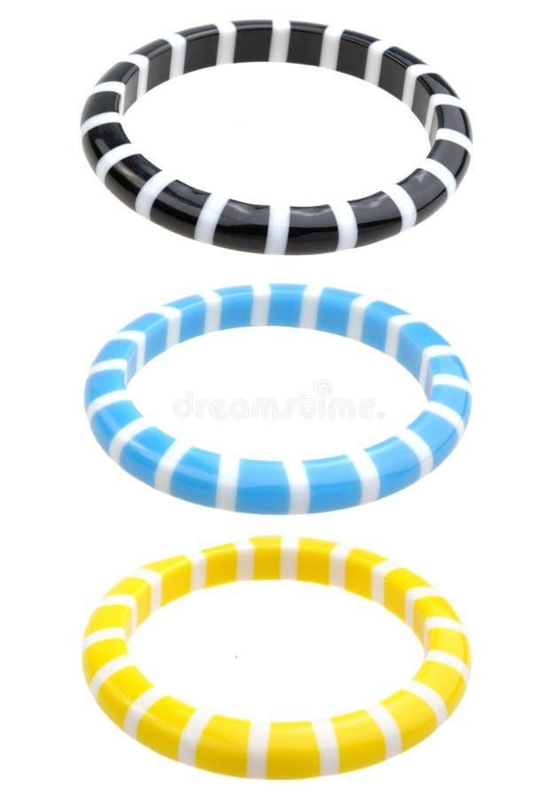 Красочные пластичные браслеты изолированные на белизне стоковое фото