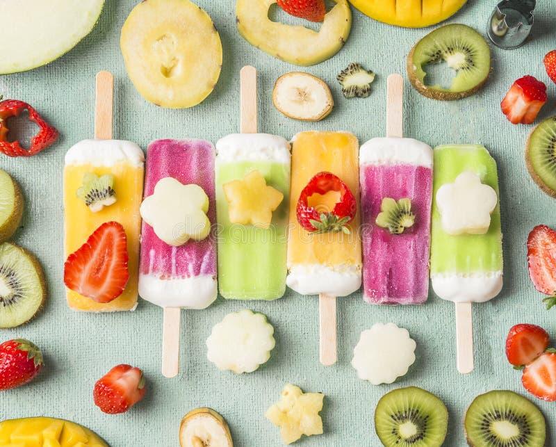Красочные различные popsicles мороженого с свежими отрезанными плодоовощами и ингридиентами ягод на свете - голубой предпосылке,  стоковое фото rf