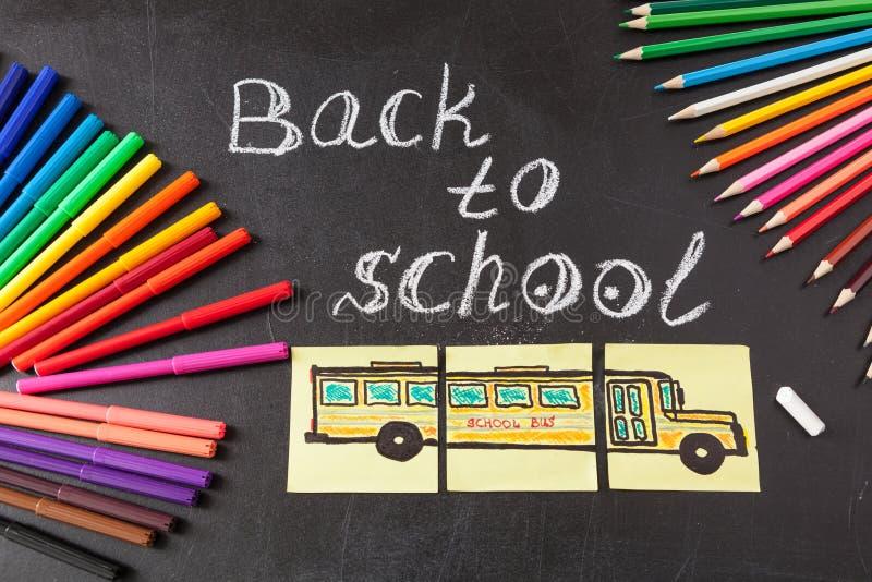 Красочные ручки, карандаши, название назад к школе написанной мелом и нарисованный школьный автобус на кусках бумаги на chalkboar стоковые фото