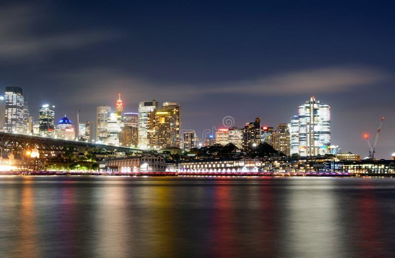 Красочные светлые отражения на воде от центрального финансового района в Сиднее, Австралии на ноче стоковое фото