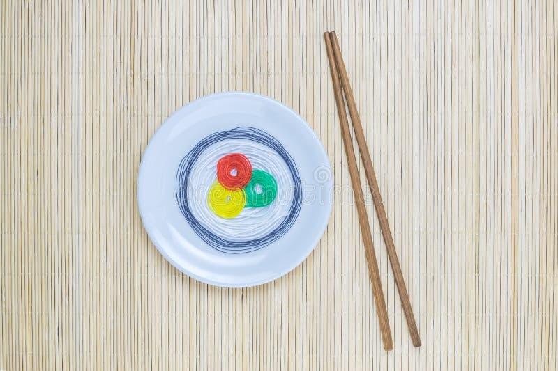 Красочные строки в форме суш на белой плите и ручках изолированных на бежевой бамбуковой предпосылке циновки соломы стоковое изображение