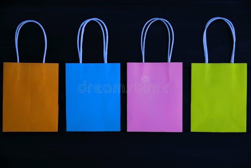 Красочные сумки подарка на темной деревянной предпосылке, взгляде сверху стоковое фото rf